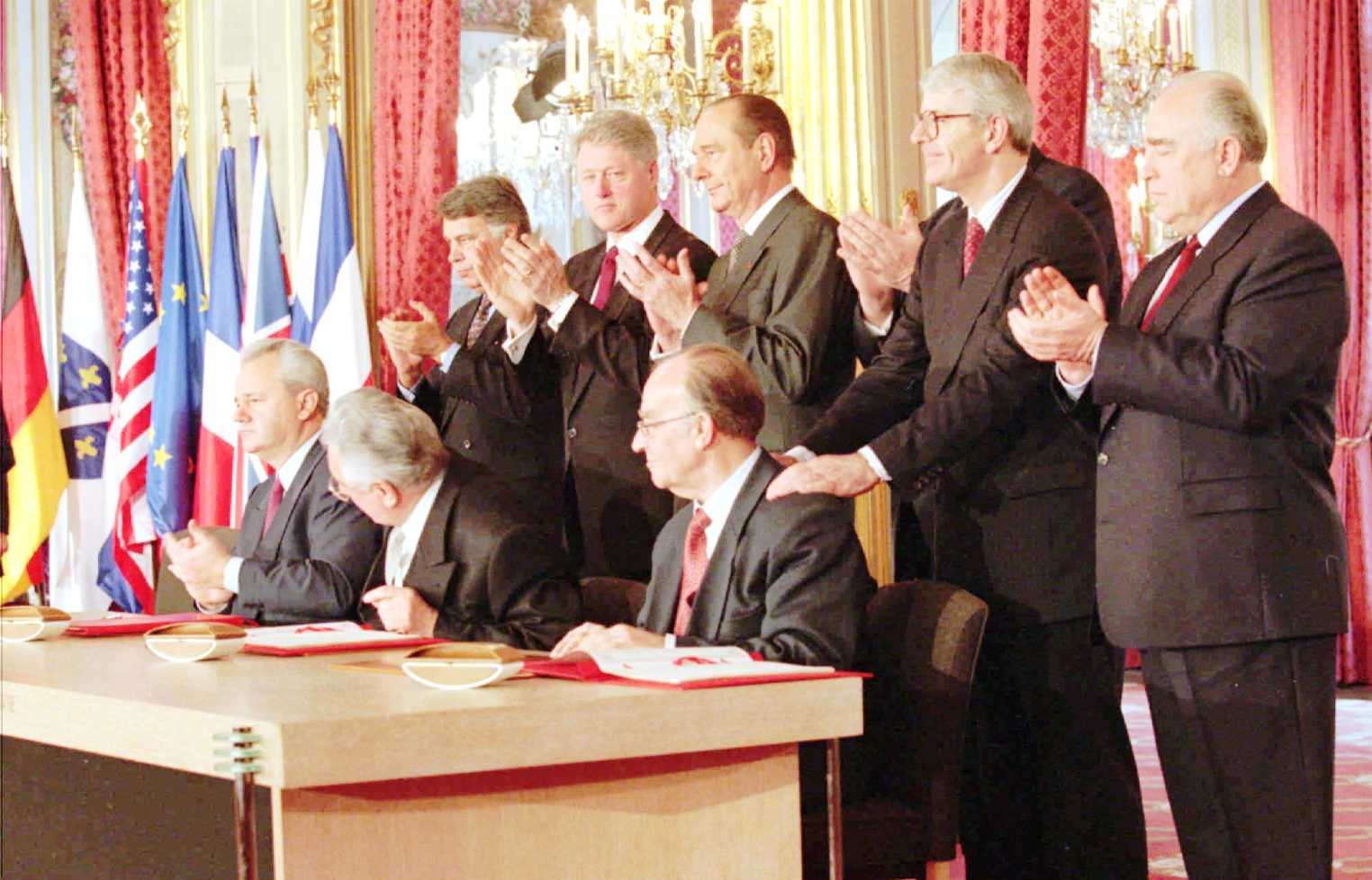 World leaders, from left, standing, Spanish Premier Felipe Gonzales, President Clinton, French President Jacques Chirac, German Chancellor Helmut Kohl, (hidden), British Premier John Major and Russian Premier Viktor Chernomyrdin, applaud the signing of the treaty to bring peace in the Balkans at the Elysee Palace, Paris, Thursday Dec. 14, 1995. Seated from left signing are Balkan leaders President Slobodan Milosevic, Serbia; Franjo Tudjman, Croatia and Alija Izetbegovic of Bosnia. (AP Photo/Jerome Delay,pool)
